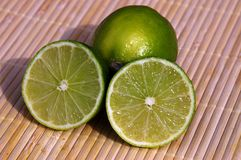Green lemons. Four green lemons on bamboo stock photo