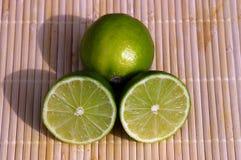 Green lemons. Four green lemons on bamboo stock image