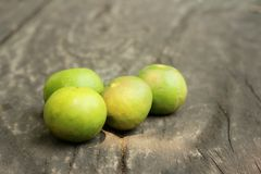Green lemons on a background of wood Royalty Free Stock Photo