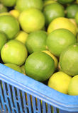 Green lemons at a fruit and vegetable market. Stock Photo