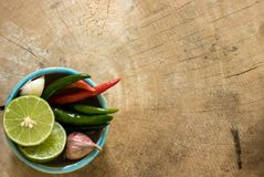 Green lemons, garlic, shallots and fresh chilli in a cup placed on a wooden. Floor Stock Photo