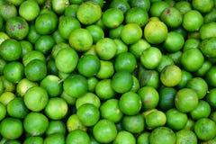 Green lemons at the market. royalty free stock image