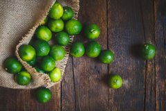 Green lemons. On the old dark background Stock Photos