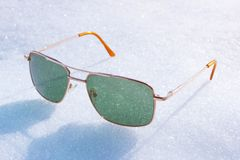 Green lens glasses on bright white snow Stock Photography