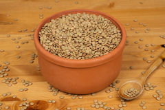 Green lentils in a pot with a wooden spoon on a wooden surface. Green lentils in a pot Royalty Free Stock Image