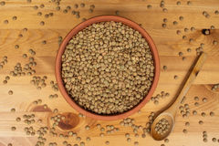 Green lentils in a pot with a wooden spoon on a wooden surface. Green lentils in a pot Royalty Free Stock Photography