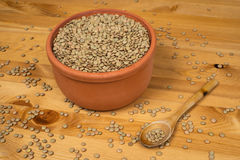 Green lentils in a pot with a wooden spoon on a wooden surface. Green lentils in a pot Stock Photos