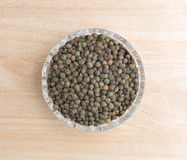 Green lentils in a small bowl on a wood table Royalty Free Stock Photo