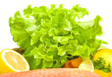 Green lettuce. Composition of green lettuce with yellow lemon, red tomato and red fish Stock Image