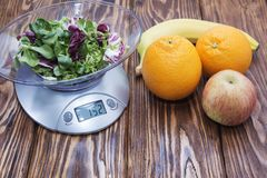 Green lettuce leaves on the kitchen scale. banana Apple orange on wooden table.  Stock Photography