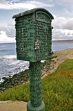 Green Lifeguard Box. A green lifeguard box rises above the ocean and cliffs Royalty Free Stock Photography