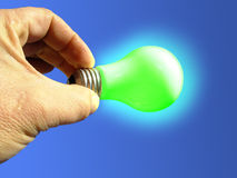 The green light. Composition of a hand holding an illuminated green light bulb against blue background royalty free stock photography