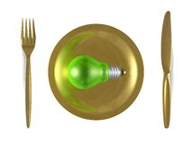 Green light bulb, golden plate, fork and knife. Top view Royalty Free Stock Images