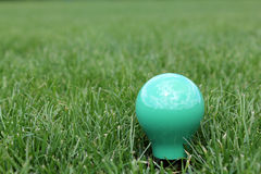 Green light bulb in grass. Green light bulb with reflection of sky sun and clouds in the green grass stock image