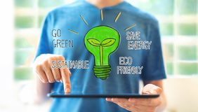 Green light bulb with man using a tablet stock illustration