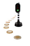 Green light for cash. Coins next to a traffic light that has turned green. Isolated on a white background stock photos
