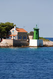 Green light house in Mali Losinj,Croatia. Green coloured light house in Mali Losinj with the pine forest in background and small stonemade house Royalty Free Stock Images