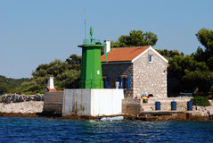 Green light house in Mali Losinj,Croatia. Green coloured light house in Mali Losinj with the pine forest in background and small stonemade home Royalty Free Stock Images