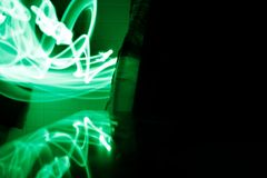 Green light painting photography - curves and waves of neon green light against a black background.  stock photos