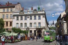 Green light rail tram on the streets of Lviv in Ukraine. Green streetcar passing the market square in Lviv in Ukraine Royalty Free Stock Image