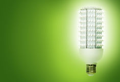 Green light(s). Bright, energy efficient light bulb consisting of 224 separate diodes, against green background royalty free stock image