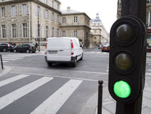 Green light says go. Parisian Traffic light lit green with traffic going by Stock Photos