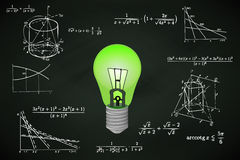Green lightbulb on blackboard with math calculations  Royalty Free Stock Photo