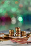 Green lights in the background like a christmas tree and money in focus. Expensive months buying gifts Stock Images