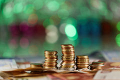 Green lights in the background like a christmas tree and money in focus. Expensive months buying gifts Stock Photos