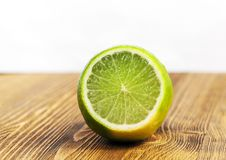 Green lime, close-up. A cut piece of sour green lime lying on a brown wooden table. Photo close-up. Focus on fruit royalty free stock images