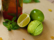 Green lime, leaves of mint, a bottle of cocktail and a plate with raisins and dried apricots on a blurred background Stock Photos
