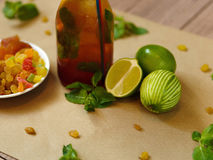 Green lime, leaves of mint, a bottle of cocktail and a plate with raisins and dried apricots on a blurred background. Royalty Free Stock Photos