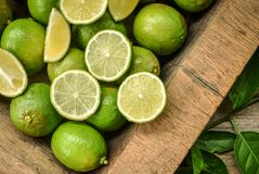Green lime for lemon tea or food ingredient. Fresh green lime with some slices and cut pieces on wooden tray background Stock Photos