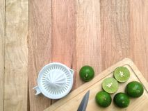 Green lime and lime crusher on wooden background. royalty free stock photography