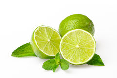 Green lime with mint leaves. Three green limes with fresh mint leaves Royalty Free Stock Photo