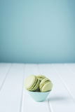 Green lime or pistachio flavored macarons in a small blue dish Stock Photo