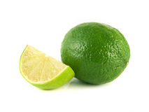 green lime with slice on white Royalty Free Stock Photos