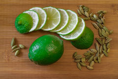 Green lime slices with cardamom. Seeds on a bamboo board stock images