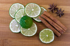 Green lime slices with cinnamon sticks and cardamom. On a bamboo board - indian spices stock photo