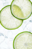 Green lime slices on the ice cubes. Top view stock image