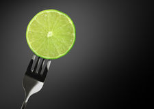 Green lime on Stainless steel fork. In studio photograph on gray background royalty free stock photo