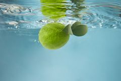 Green lime in water on a blue background. Round green lime with leaves falling into the water making bubbles and waves on the water on a blue background royalty free stock image