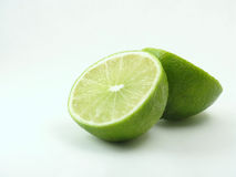 Green lime on white cut in half. A fresh green lime is cut in half, on white background Stock Photo
