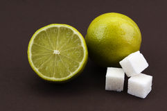 Lime and sugar cubes on a brown background Stock Photo