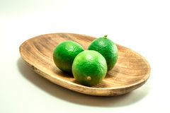 Green lime on wooden tray royalty free stock photo