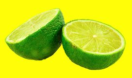 Green Lime On Yellow Background stock photography