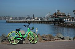 A green Limebike is parked in front of San Diego`s Seaport Village royalty free stock images