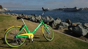 A green Limebike is parked at San Diego Bay stock photography