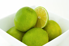 Green limes in a bowl. Whole green limes and a half of a lime in white porcelain bowl. Isolated on white background Royalty Free Stock Image