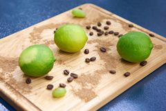 Green limes and coffee beans on wooden cutting board. Green limes and coffee beans on a wooden cutting board Royalty Free Stock Images